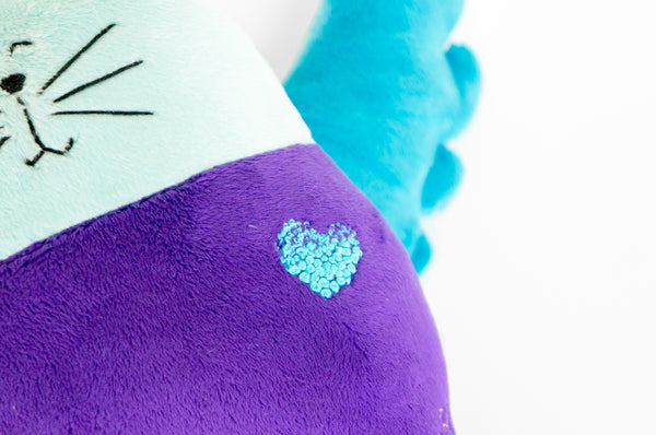 Close up of a stuffed cat with a hand stitched heart