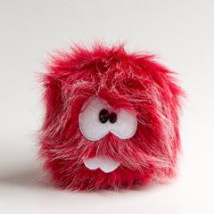 Red stuffed monster with two teeth