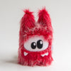 Red plush monster with two big eyes and three teeth