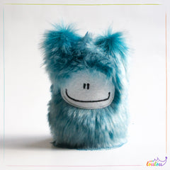Blue stuffed monster with a big smile