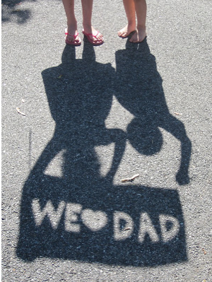 Shadow of two little girls holding a We love dad sign