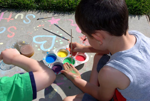 kid painting sidewalk with homemade chalk