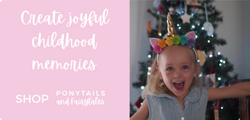 Little girl dressed in bright rainbow unicorn horn at christmas
