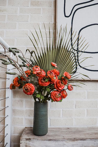 A faux flower and foliage arrangement with orange ranunculus and a green palm frond in a dark green handmade vase.