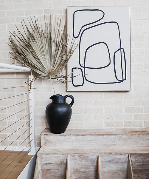 A large black vase with a huge dried palm frond on a cream brick background.