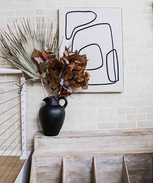 A large black vase with a huge dried palm frond and rust coloured maple leaves on a cream brick background.