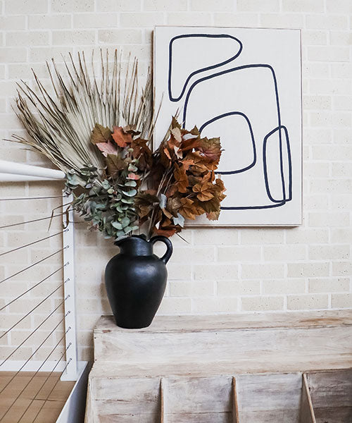A large black vase with a huge dried palm frond, a rust coloured maple leaves, and silver dollar eucalyptus  on a cream brick background.