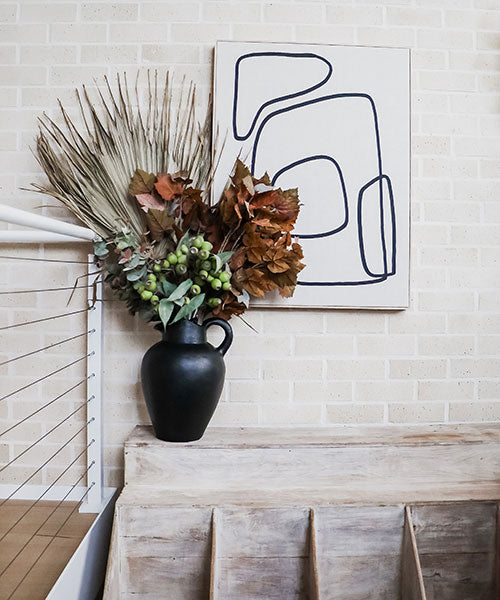 A large black vase with a huge dried palm frond, a rust coloured maple leaves, silver dollar eucalyptus, and green eucalyptus gumnuts on a cream brick background.
