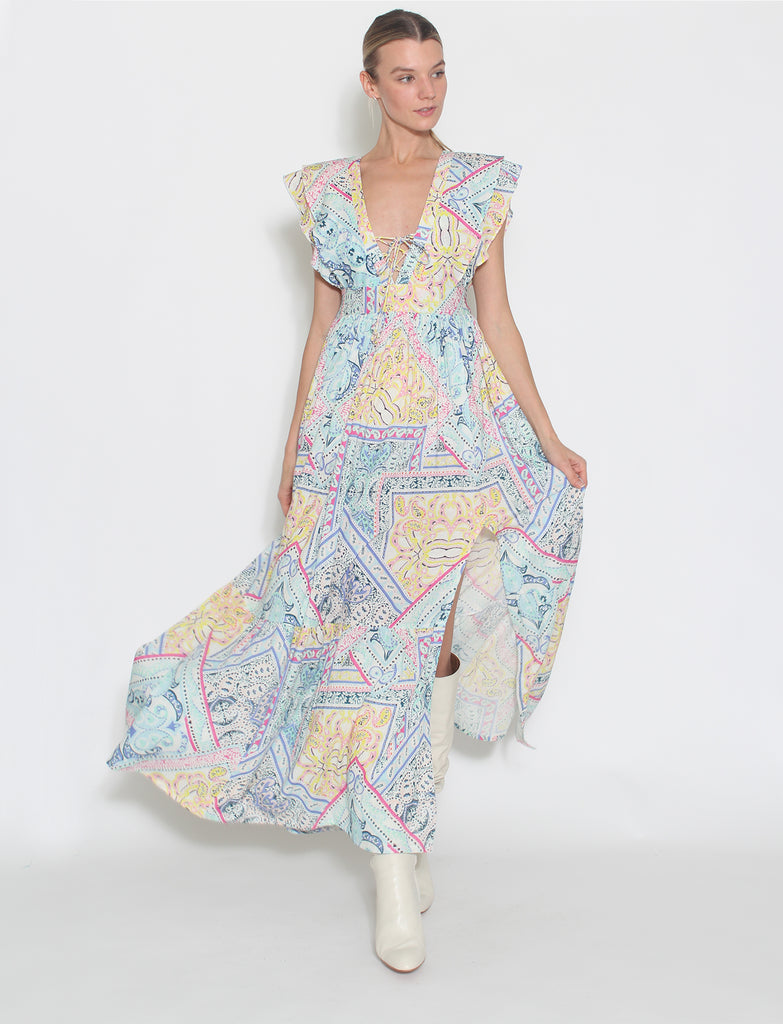 A blue heather paisley print maxi dress with an empire waist and low-cut v-neckline. This dress has a fitted bodice that transforms into a breezy flounce with a front slit. This dress is made to strut in and exudes confidence. The pastel colors give it a cool and calming vibe, while the frills around the armholes give it a feminine touch.