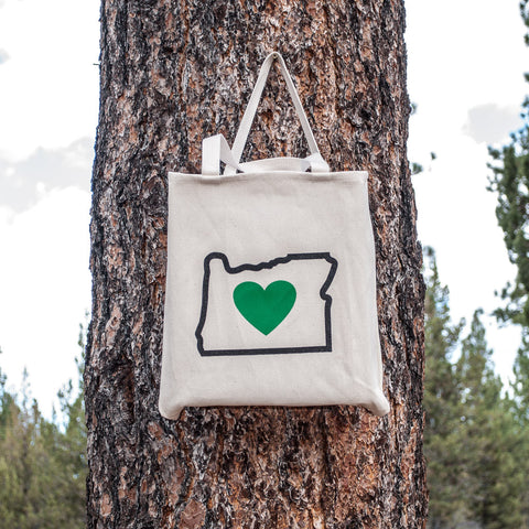 Canvas tote bag featuring the shape of Oregon with a green heart in the middle.