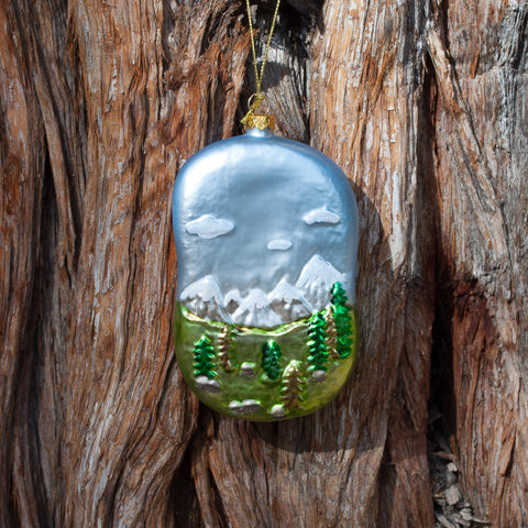 An oval glass Christmas ornament that depicts the Cascade Mountains and reads Bend, Oregon.