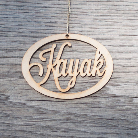 A oval, laser cut, birchwood Christmas ornament that reads Kayak.
