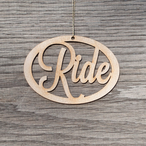 A oval, laser cut, birchwood Christmas ornament that reads Ride.