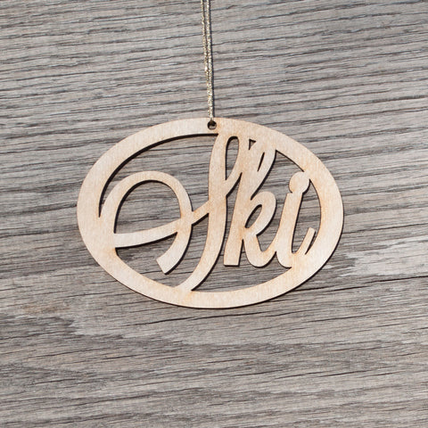 A oval, laser cut, birchwood Christmas ornament that reads Ski.