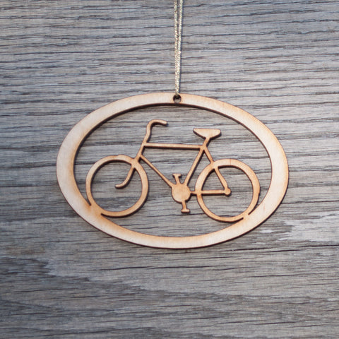 An oval, laser cut, birch wood Christmas ornament that includes the shape of a bike.