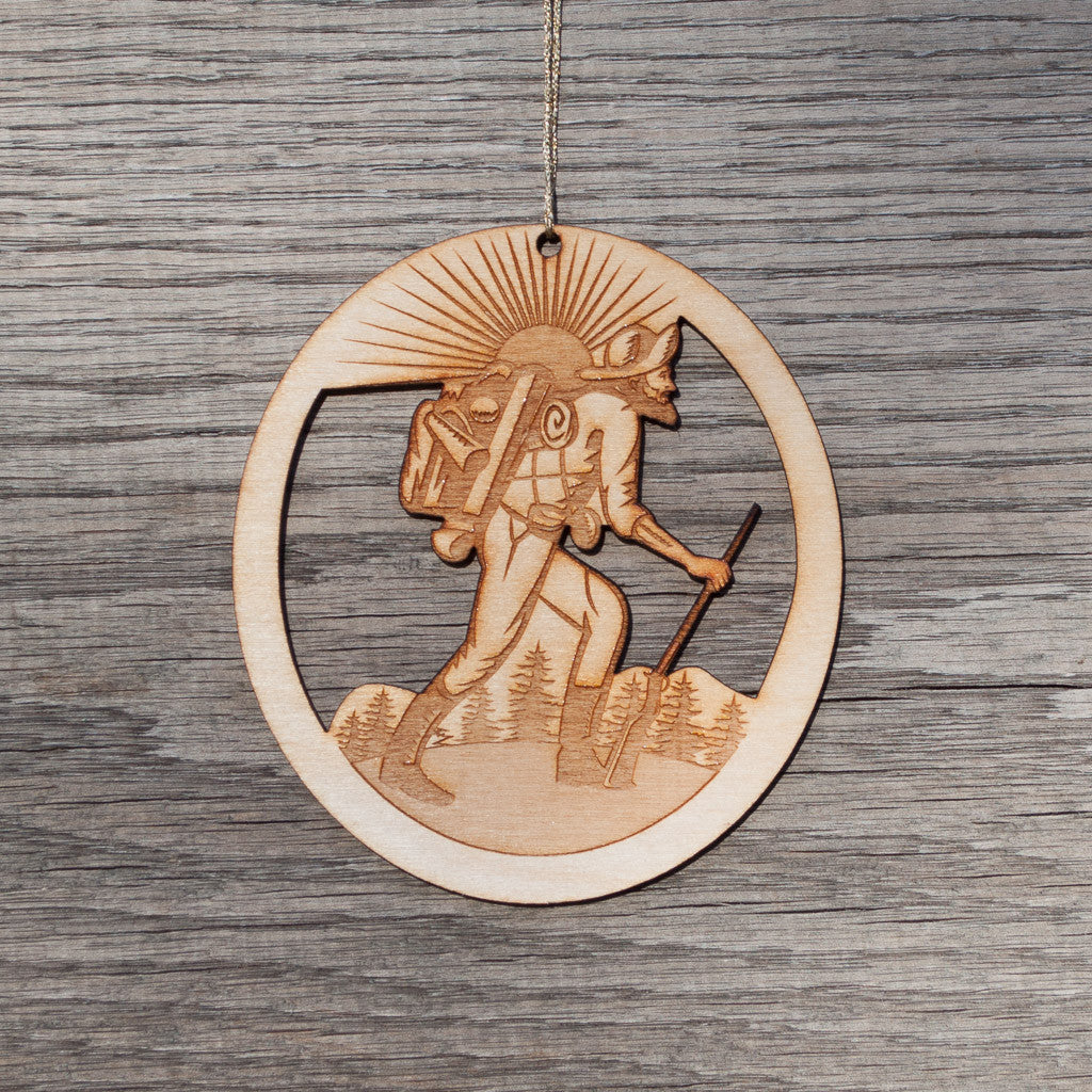 A oval, laser cut, birchwood Christmas ornament that depicts a hiker.