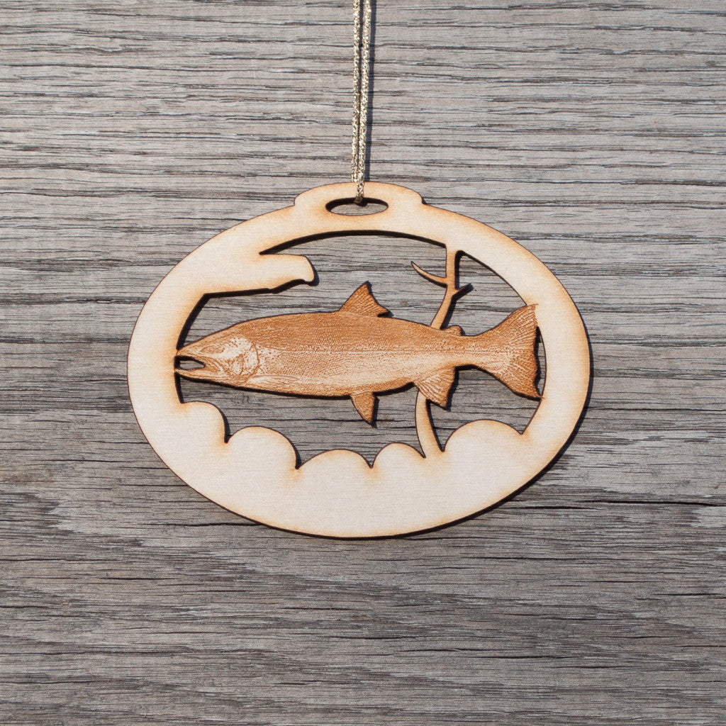 A oval, laser cut, birchwood Christmas ornament that depicts a steelhead trout.
