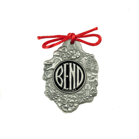 A decorated pewter ornament with the BEND logo in the middle and a red bow at the top.