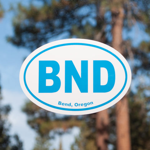 Oval, light blue and white souvenir decal that reads, BND, Bend, Oregon.