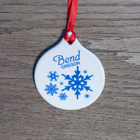 A round white ceramic ornament with blue snowflakes and the words Bend, Oregon.