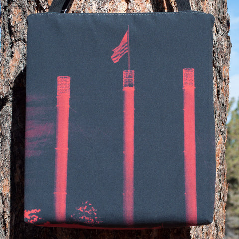 Large tote bag with a full-bleed picture of the REI smokestacks in the Old Mill at night.