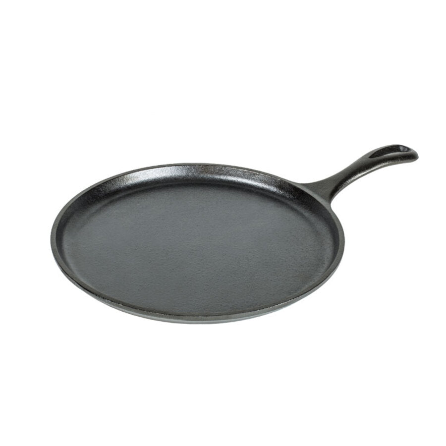 A side view of a round black cast iron griddle with a handle.