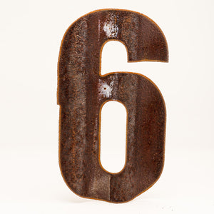 A rusty corrugated metal number six.