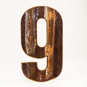 A rusty corrugated metal number nine.