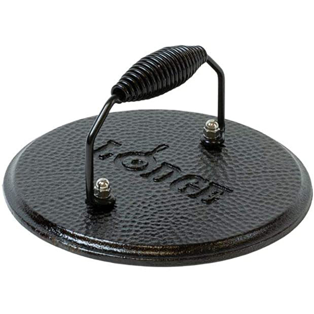 A side view of a round black cast iron grill press with handle.