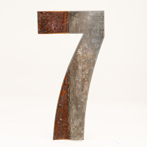 A rusty corrugated metal number seven.
