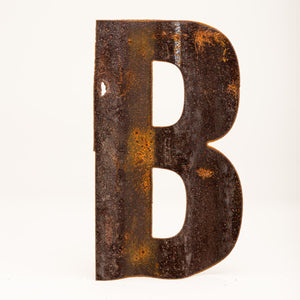 A rusty corrugated metal letter B.