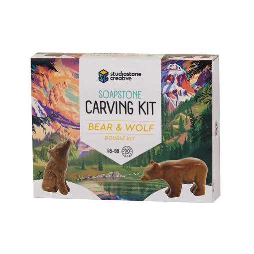 The front of a box with an illustrated BC landscape and soapstone carvings of a wolf and a bear on it.