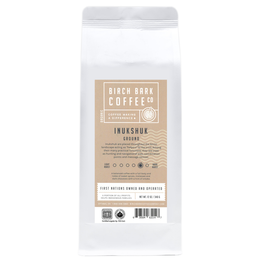 A white bag of coffee grounds with a tan label written in english.