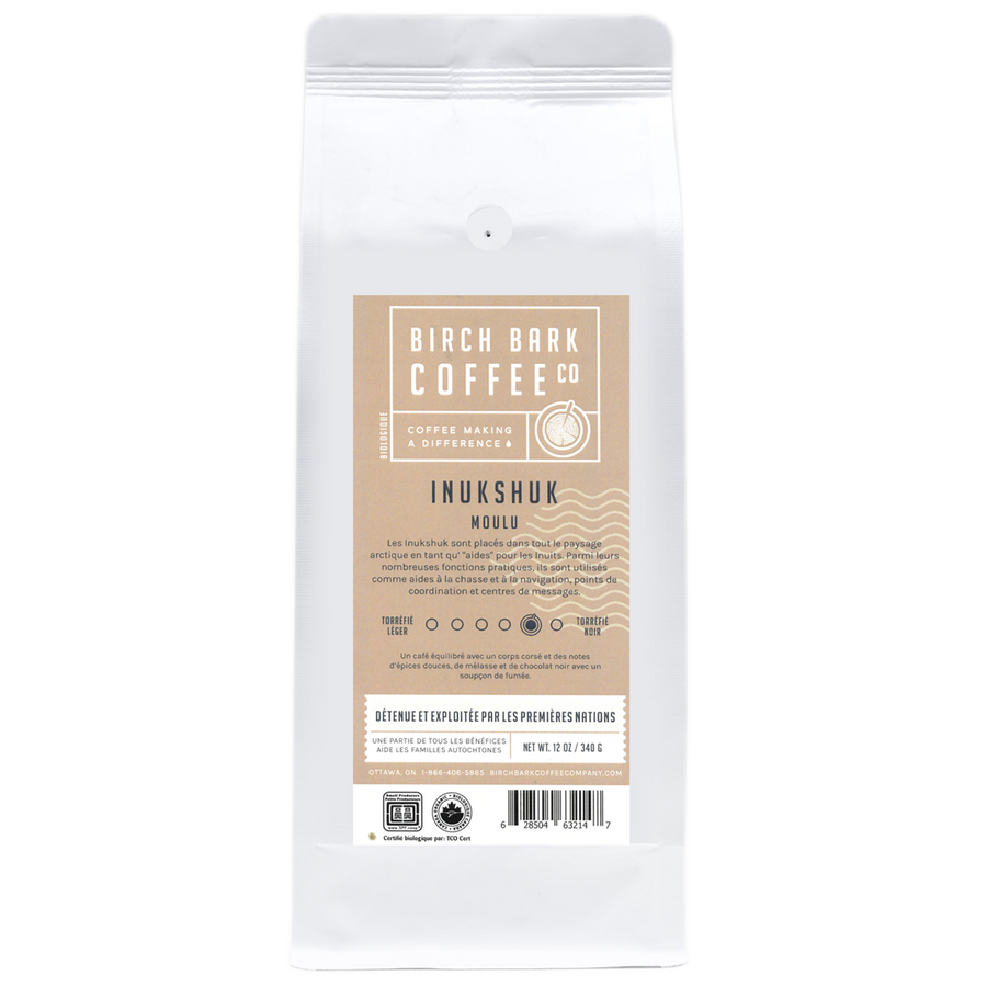 A white bag of coffee grounds with a tan label written in french.