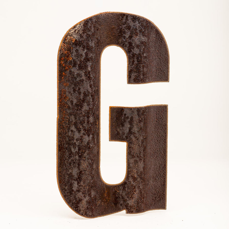 A rusty corrugated metal letter G.