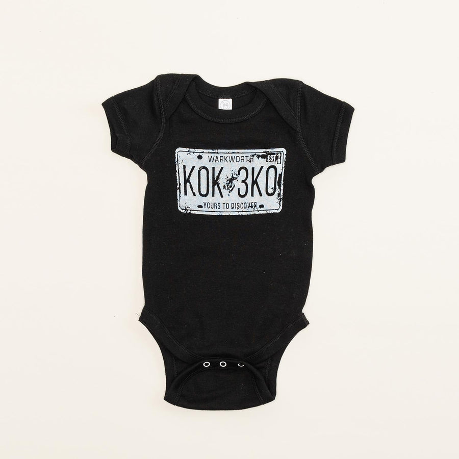 "A black baby onesie with a graphic of a licence plate on it. The licence plate is stamped ""Warkworth, K0K 3K0, yours to discover""."