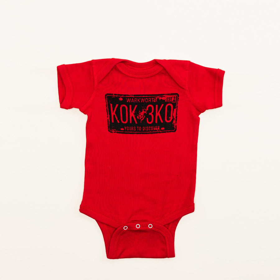 "A red baby onesie with a graphic of a licence plate on it. The licence plate is stamped ""Warkworth, K0K 3K0, yours to discover""."