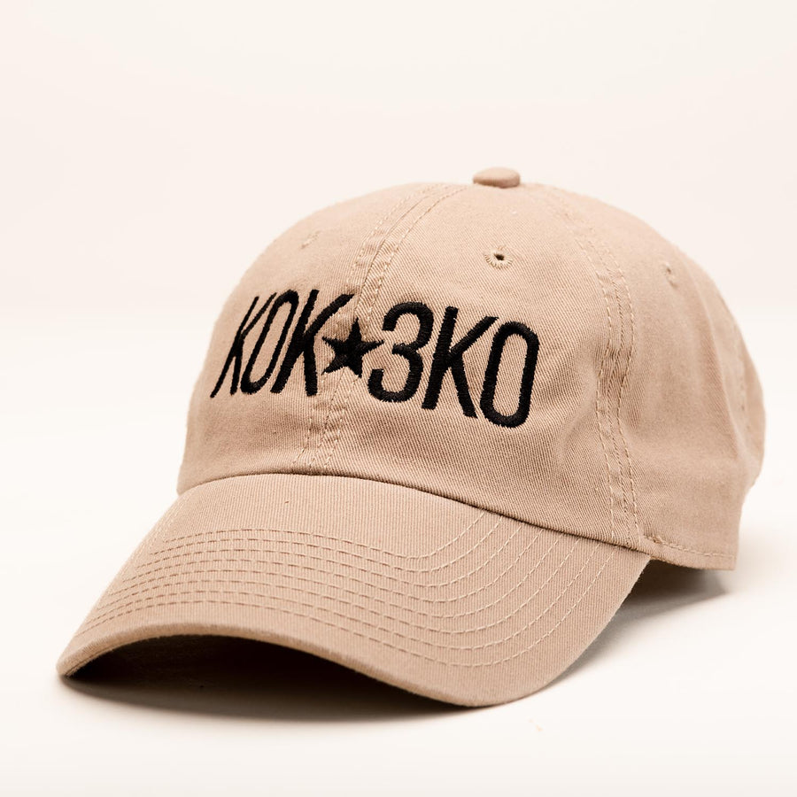 "A tan ballcap with ""K0K 3K0"" stitched in black on the front."