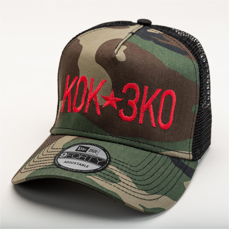 "A black mesh backed camouflage ballcap with ""K0K 3K0"" stitched in red on the front."
