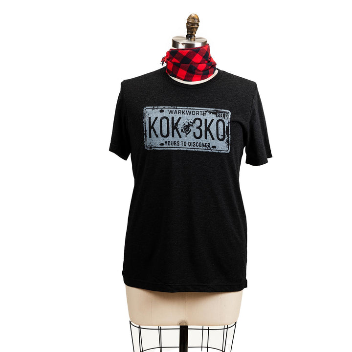 "A grey short sleeve shirt with a graphic of a white licence plate, the plate says ""Warkworth K0K 3K0 yours to discover""."