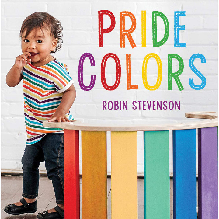 The cover of book depicting the title and a child standing by a rainbow coloured desk.