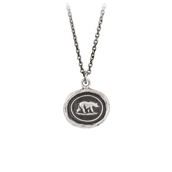 A sterling silver necklace inscribed with an image of a bear walking.