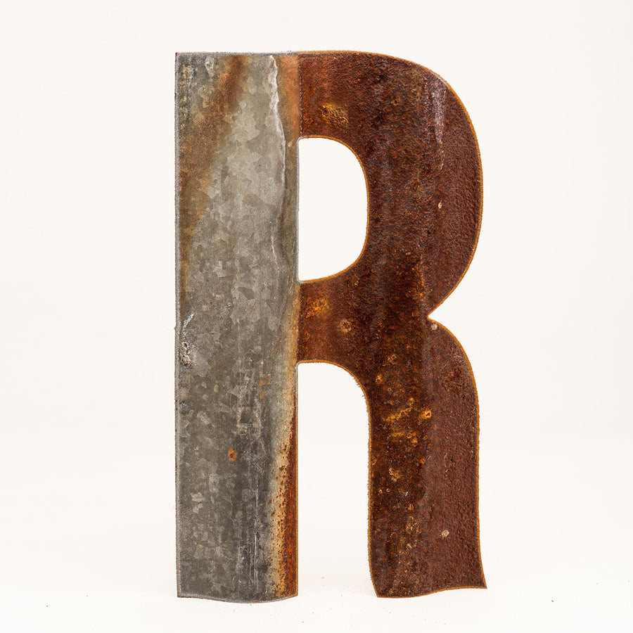 A rusty corrugated metal letter R.