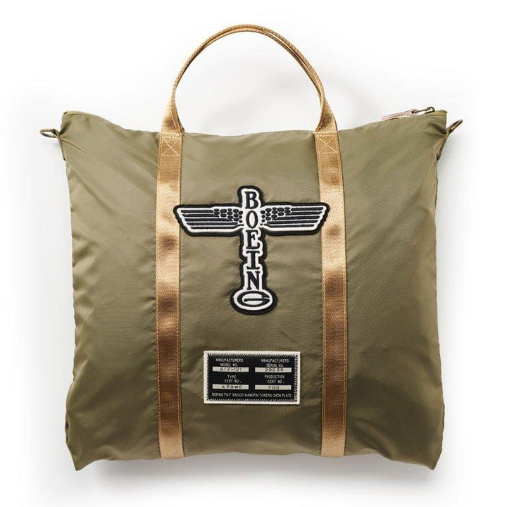 "A army green helmet bag with ""Boeing"" logo and manufactures plate patches on it."