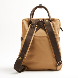The back of the tan back pack, showing off the brown straps.