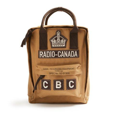 "A tan backpack with brown straps decorated with ""Radio Canada"", ""CBC"", and crown patches."