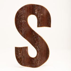 A rusty corrugated metal letter S.