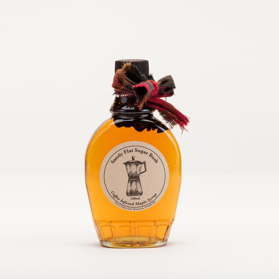A bottle of maple syrup with coffee beans in it and a tartan ribbon tied around the neck.