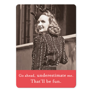"A rectangular magnet with a photo of a woman looking over her shoulder and a coral bar at the bottom with the words ""Go ahead, underestimate me. That'll be fun."" on it."