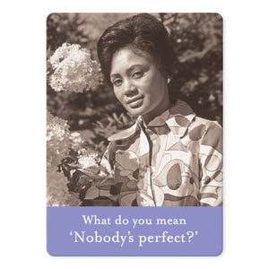 "A rectangular magnet with a photo of a women standing beside a lilac bush and a purple bar at the bottom with the words ""What do you mean 'Nobody's perfect?'"" on it."